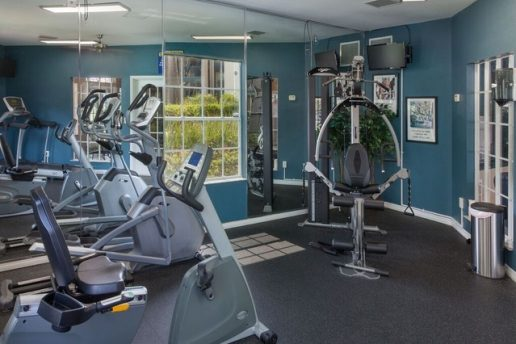 Fitness center with multiple workout machines and mirrored wall