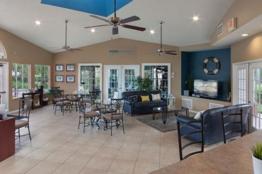 Lounge area with seating, ceiling fans and TV