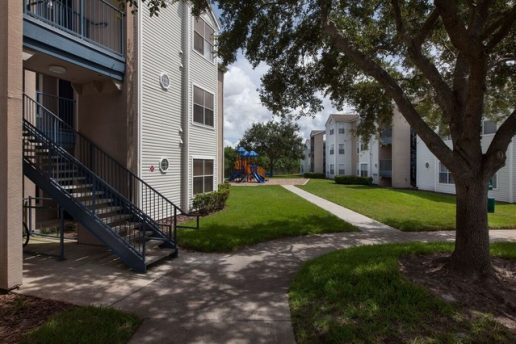 Exterior of Acclaim at Conroy with trees and stairs leading up to apartments